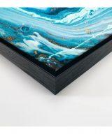 Tableau abstrait bleu clair avec un cadre noir charbon présenté de coté